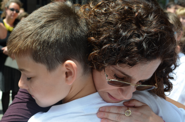 Dana Lerner embraces Jonathan Hume, who along with his twin brother Jacob, eulogized their former classmate Cooper Stock at a recent street renaming ceremony. Photo by Daniel Fitzsimmons.