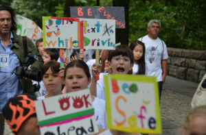 "Calhoun School students march in memory of former classmate Cooper Stock, who was killed by a reckless cab driver last January. The students called themselves ""Cooper's Troopers"" and carried homemade signs highlighting safe driving. Photo by Daniel Fitzsimmons."